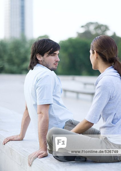 Junges Paar sitzend im Stadtpark