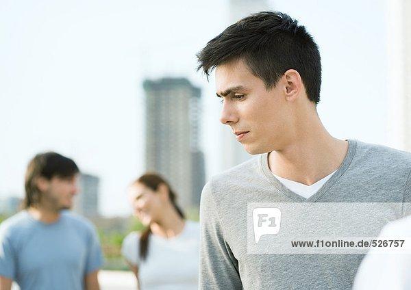 Junger Mann schaut zur Seite  junges Paar im Hintergrund