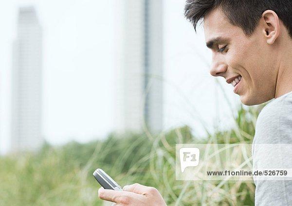 Junger Mann schaut aufs Handy und lächelt im Stadtpark
