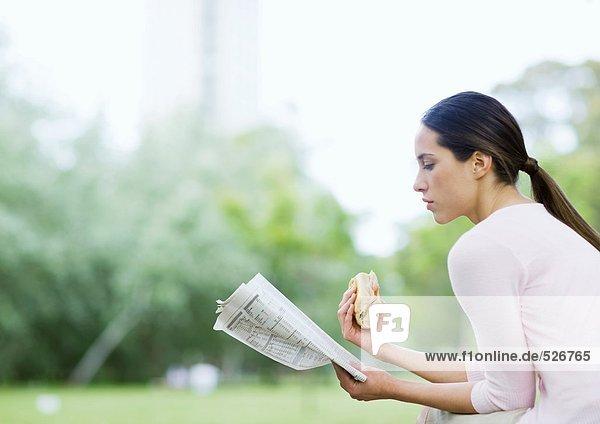 Junge Frau liest Zeitung und hält ein Sandwich im Stadtpark.