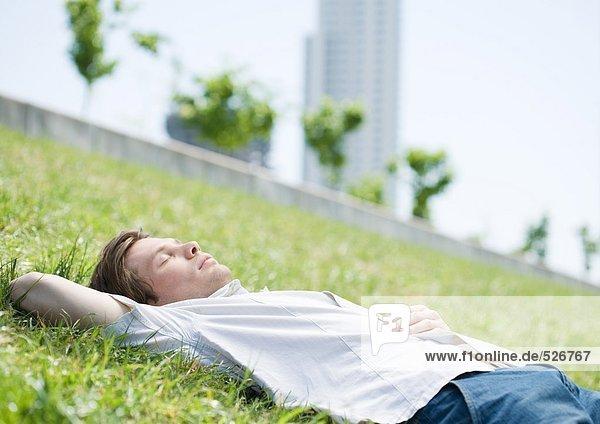Junger Mann liegt auf Gras im Stadtpark