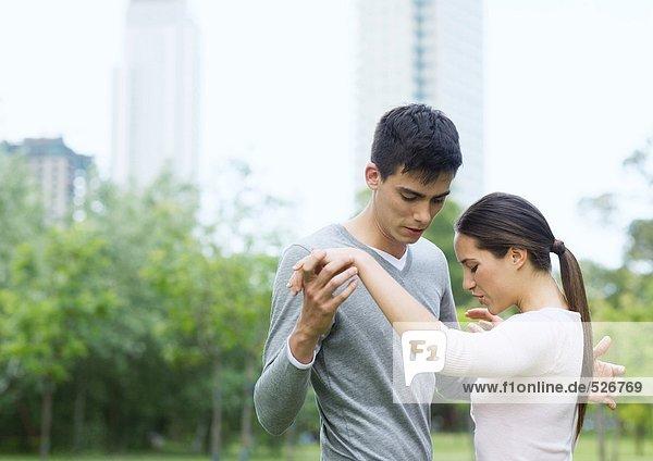 Junge Frau bringt dem jungen Mann das Tanzen im Stadtpark bei