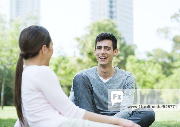 Junges Paar sitzt zusammen im Stadtpark