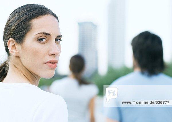 Junge Frau schaut im Stadtpark über die Schulter
