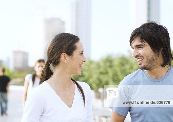Junges Paar lächelt sich im Stadtpark an