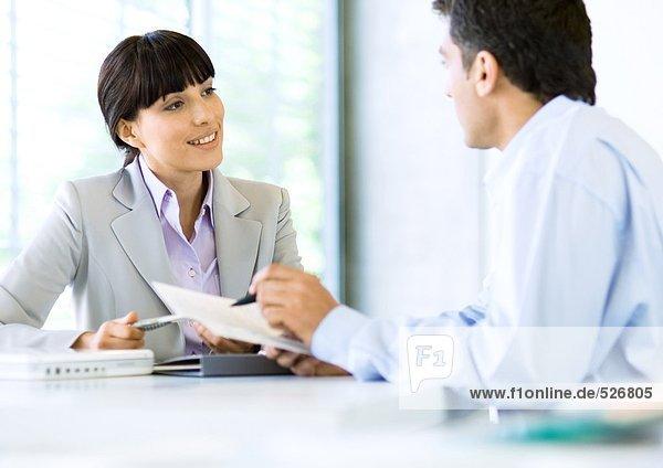 Geschäftsmann im Gespräch mit Geschäftsfrau und Holding-Dokument