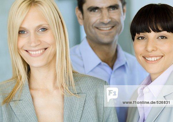Blonde Geschäftsfrau mit zwei Mitarbeitern  Portrait