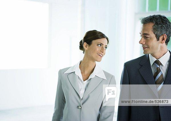 Geschäftsfrau lächelt männliche Kollegin an