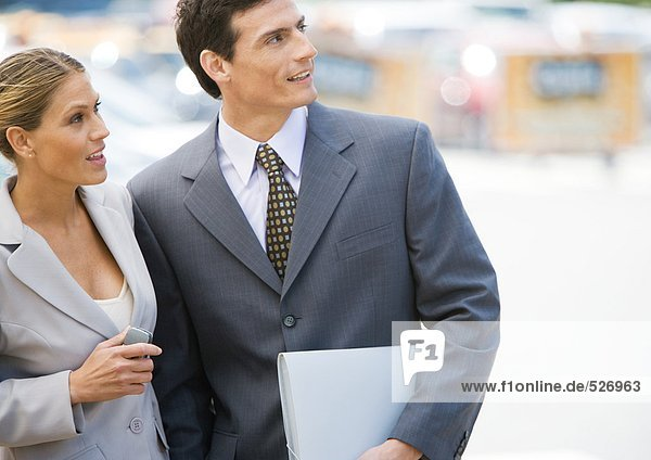 Geschäftsfrau und Mann stehen dicht beieinander und schauen nach oben.