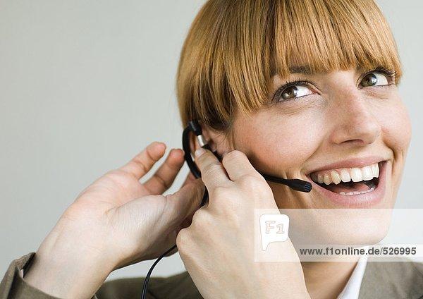Frau lächelt und setzt Headset auf