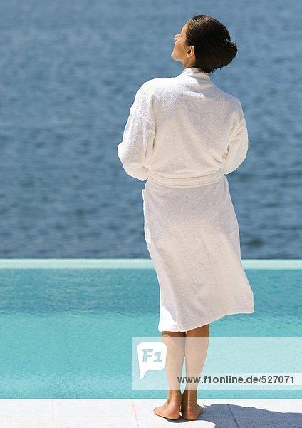 Frau im Bademantel am Pool mit Blick aufs Meer  Rückansicht