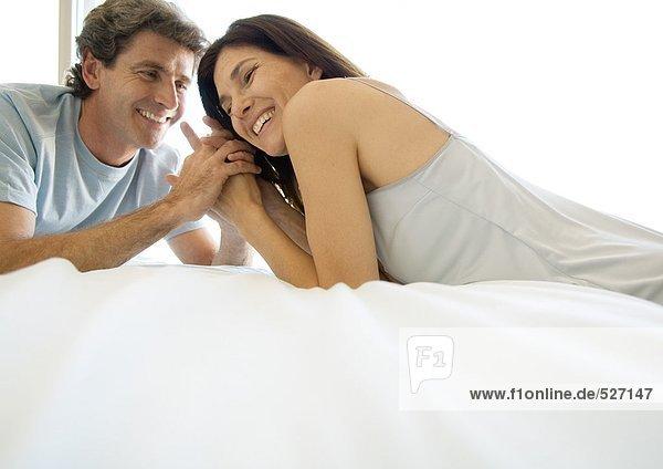 Erwachsenes Paar liegt von Angesicht zu Angesicht auf dem Bett.