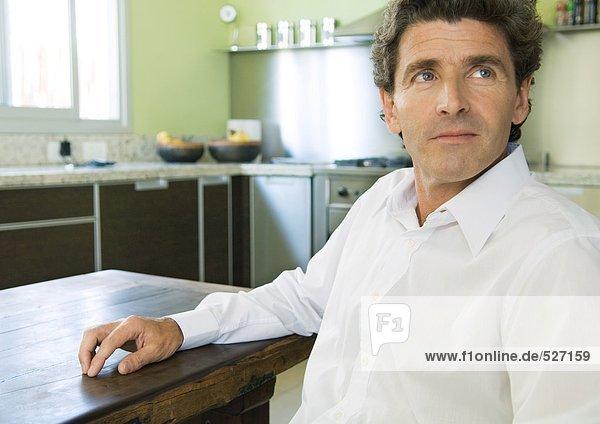 Erwachsener Mann in der Küche sitzend