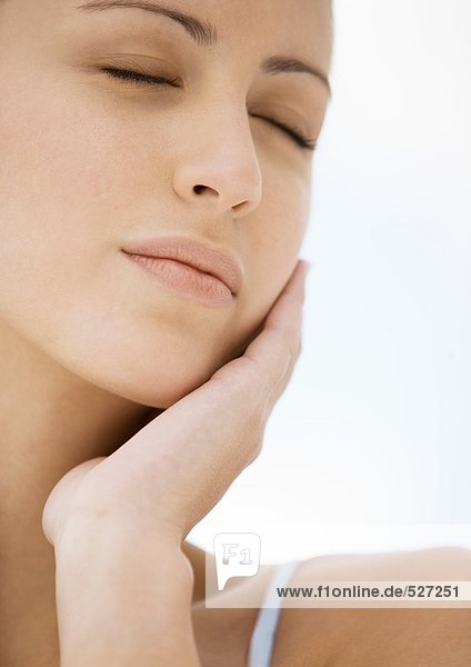 Woman resting face on hand with eyes closed