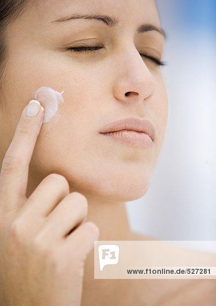 Woman applying moisturizer to cheek  eyes closed