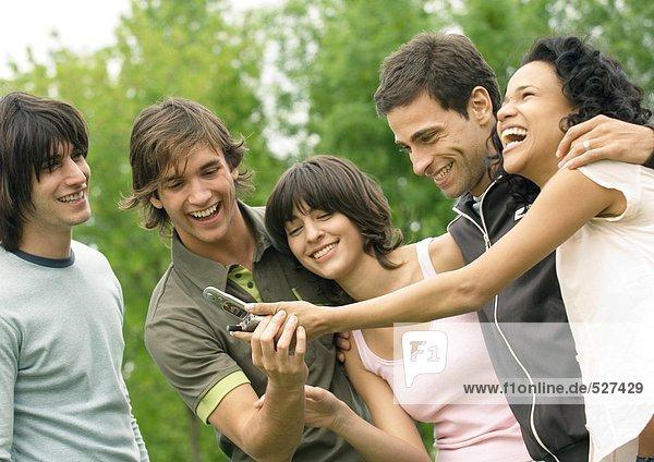 Gruppe junger Freunde,  die lachen und das Handy anschauen