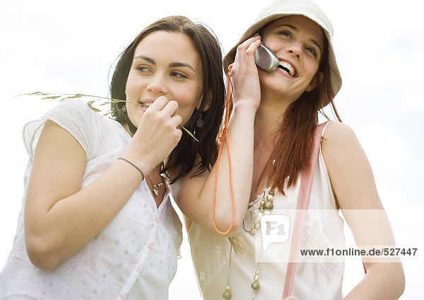 Two young woman outdoors  one using cell phone