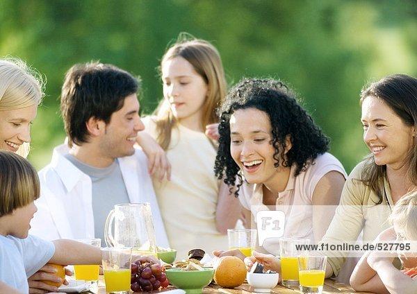 Familie im Freien am Tisch sitzend