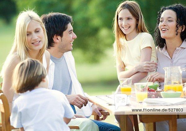 Familie und Kinder sitzen am Tisch im Freien