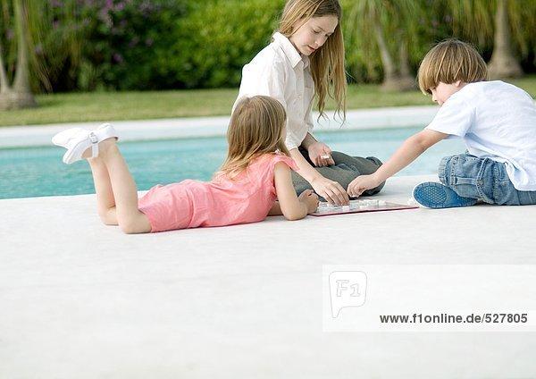 Drei Kinder beim Brettspiel am Poolrand