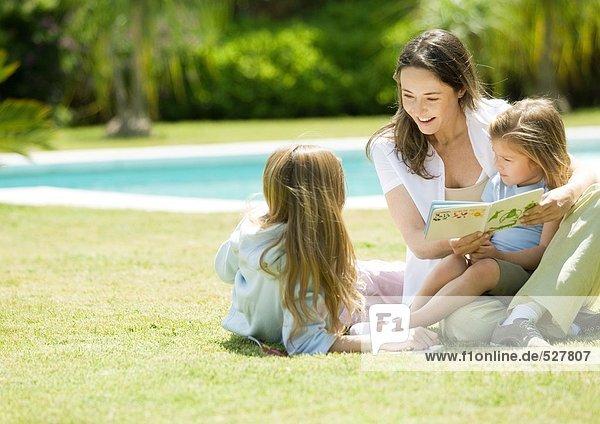 Mutter liest Buch für zwei Töchter