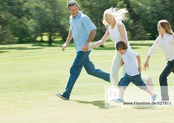 Familie hält sich an den Händen und rennt über das Gras.
