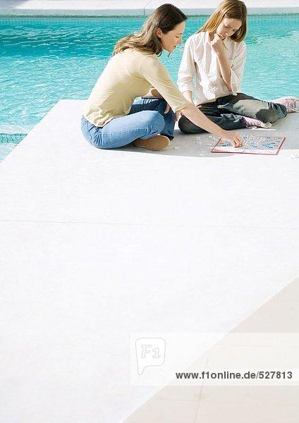 Mutter und Tochter sitzen am Poolrand  spielen Brettspiel