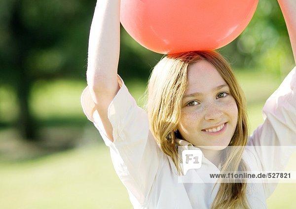 Mädchen mit Ball auf dem Kopf