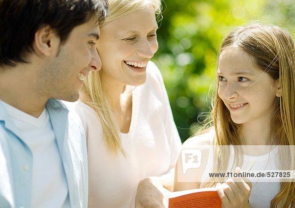 Mädchen hält Buch  lächelt die Eltern an.