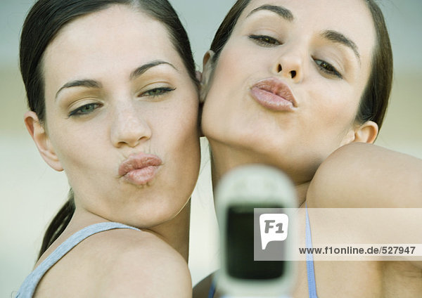 Two young women posing and puckering toward cell phone