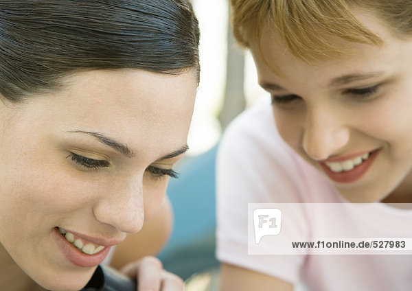Young woman and girl looking down and smiling  portrait  extreme close-up