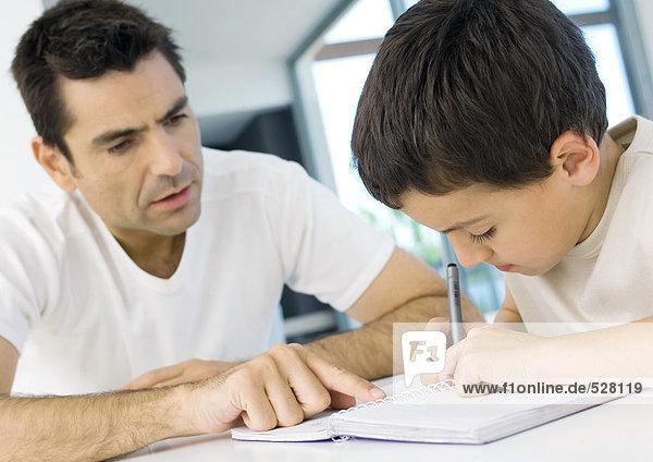 Junge  der mit Vaters Hilfe Hausaufgaben macht  abgeschnitten