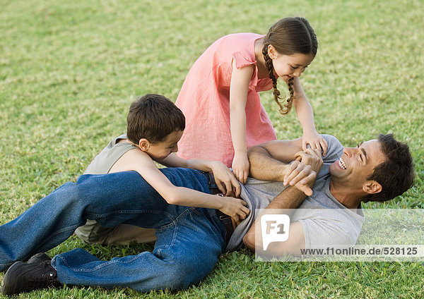 Boy and girl tickling father on grass