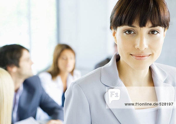 Businesswoman smiling at camera  meeting in background  portrait