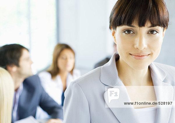 Geschäftsfrau lächelt vor der Kamera  Treffen im Hintergrund  Portrait