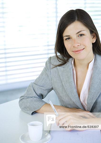 Geschäftsfrau am Tisch sitzend mit Stift und Tasse Kaffee  lächelnd vor der Kamera