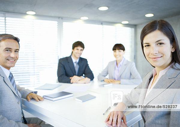 Führungskräfte sitzen am Tisch und lächeln vor der Kamera.