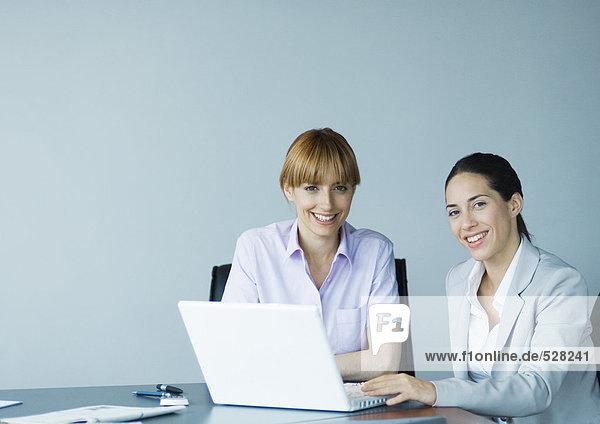 Zwei Geschäftsfrauen mit Laptop  lächelnd vor der Kamera