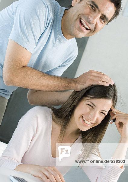 Paar lachend  Mann mit Händen auf dem Kopf der Frau