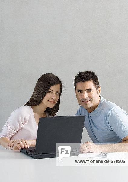 Paar mit Laptop  lächelnd in der Kamera
