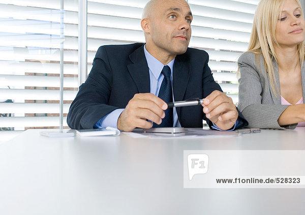 Zwei Geschäftsleute  die während des Meetings zuhören