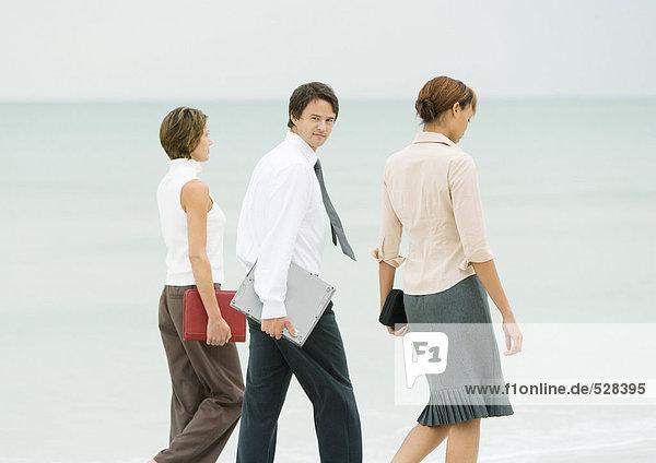 Business-Team beim Spaziergang am Strand  Geschäftsmann schaut über die Schulter auf die Kamera