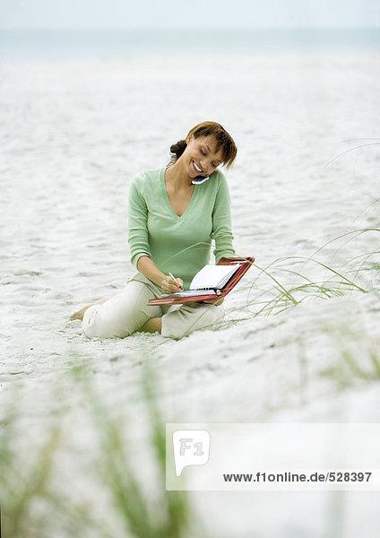 Frau sitzt auf Sand  benutzt Handy und schreibt in der Agenda