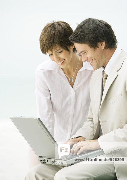 Geschäftsmann und Frau nutzen gemeinsam den Laptop