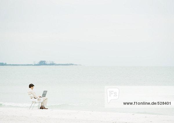 Geschäftsmann mit Laptop am Strand  Mittelstrecke