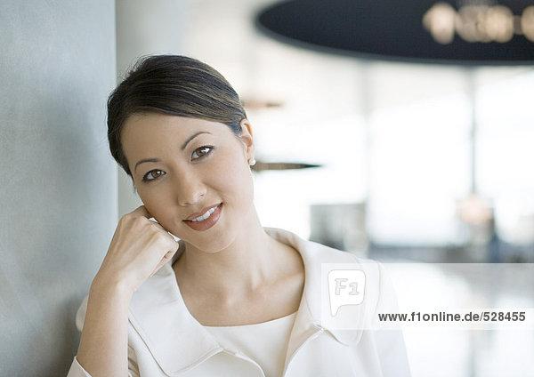 Reisende Frau lehnt Kopf an Hand im Flughafen  lächelt in die Kamera