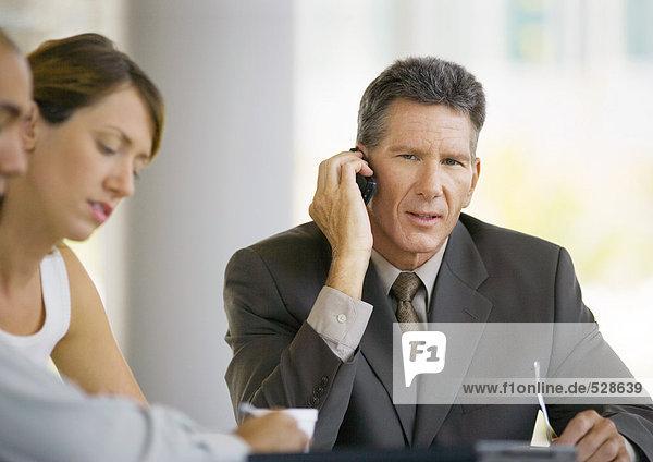 Geschäftsmann mit Handy  sitzend in der Nähe von Kollegen