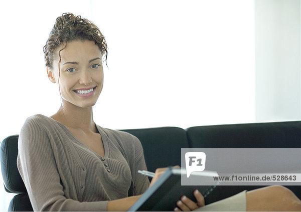 Frau schreibt in Notizbuch  lächelt in die Kamera Frau schreibt in Notizbuch, lächelt in die Kamera
