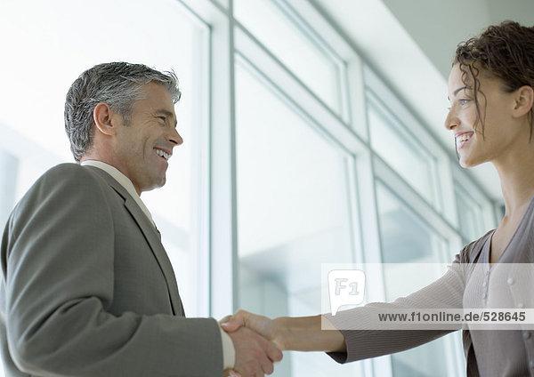 Geschäftsmann beim Händeschütteln mit Frau Geschäftsmann beim Händeschütteln mit Frau