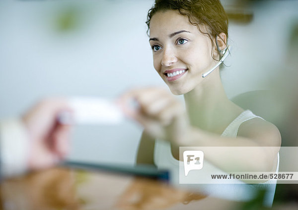 Empfangsdame übergibt Karte an den Kunden Empfangsdame übergibt Karte an den Kunden